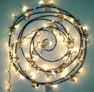twinkly lights in a spiral on the wall with candleholders